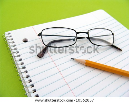 note book with pencil and glasses