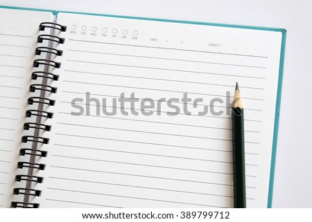 Note book with pencil on a  white background