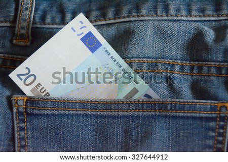 note of 20 euro on the pocket of blue jeans, detail - stock photo