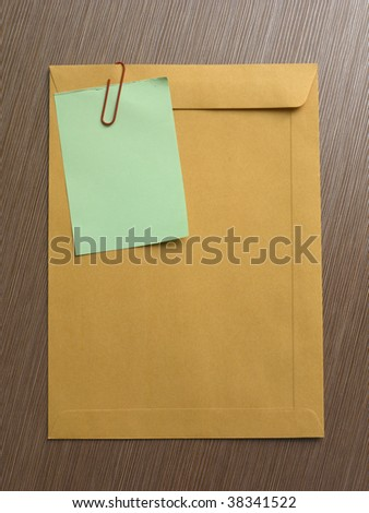 note on the big brown envelop on the table top - stock photo