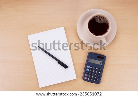 note pad with pen, calculator and cup of coffee on desk