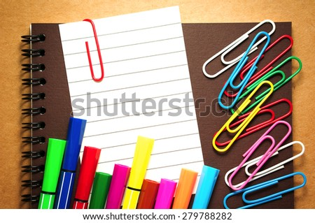 Note paper clip on notebook with colorful marker pens and paperclips on brown cardboard background - stock photo
