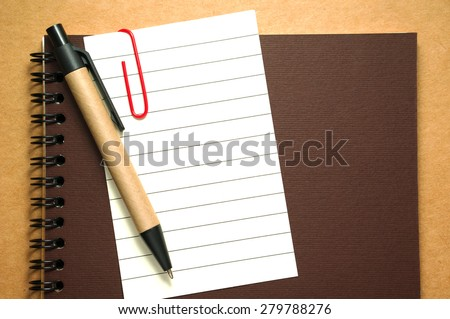 Note paper clip on notebook with pen on brown paper cardboard background - stock photo