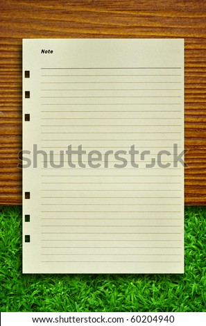 Note Paper on wood and grass for text an background