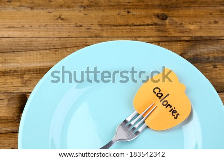 Note paper with message  attached to fork, on plate, on wooden background - stock photo