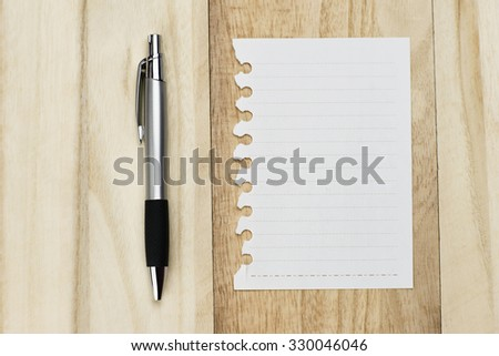 note paper with pen on wooden table - stock photo