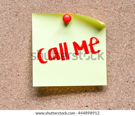 Note with Call me inscription. Sticky note with Call me inscription pinned on a cork bulletin board. - stock photo
