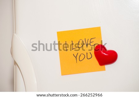 "Note with handwritten ""I Love You"" with heart magnet on a fridge door - stock photo"