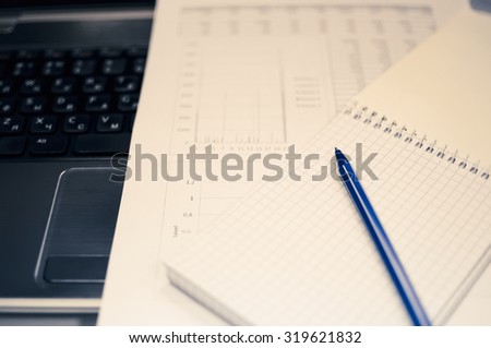 Notebook an address book with blank sheets and the handle lie on the laptop. Business a concept idea about a Split toning in cold shades of color. - stock photo