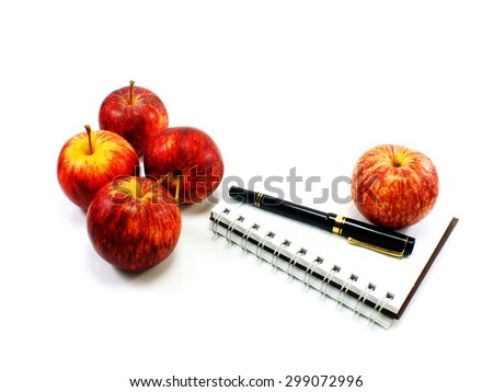 notebook and apples on white background