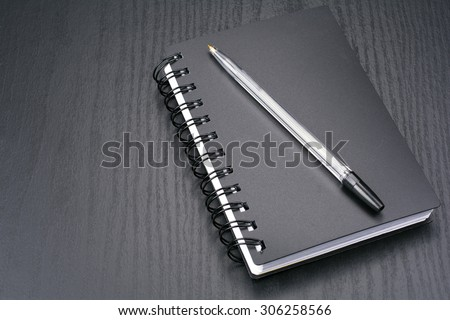 Notebook and ballpoint pen on the black desk - stock photo
