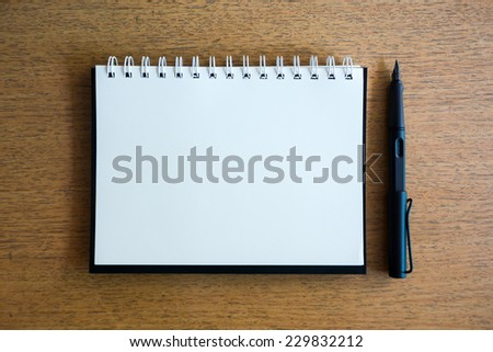 notebook and black pen on wood desk - stock photo