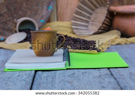Notebook and coffee cup in areas classified as vintage. - stock photo