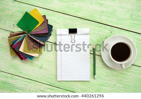 notebook and colored fabric. notebook with cup of coffee on wooden green background - stock photo