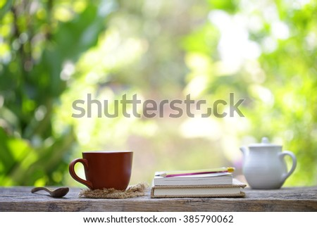Notebook  and cup mini vintage teapot with flower on wooden table