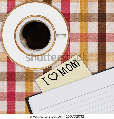 notebook and cup of coffee on picnic tablecloth - stock photo