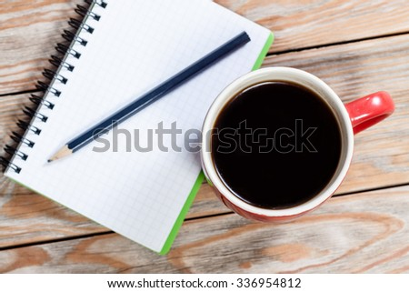 Notebook and cup of coffee on wooden table. Business concept.