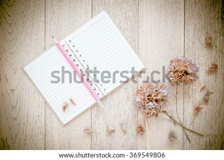 Notebook and Dry flowers on old wood background. Vintage Style. - stock photo