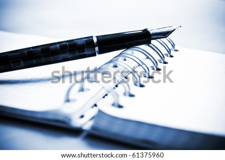 Notebook and fountain pen in composition in blue tone - stock photo