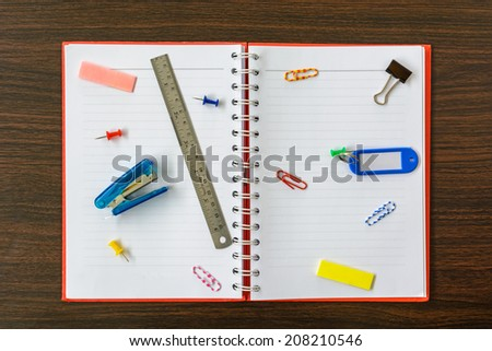 notebook and office equipment on wooden table - stock photo