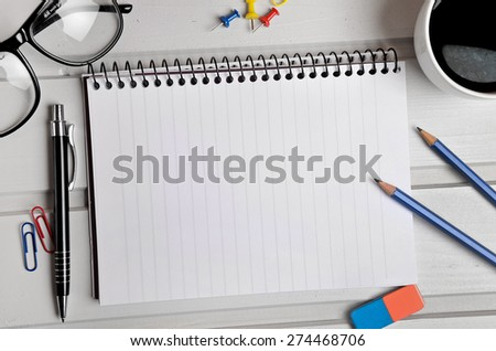 Notebook and office supplies on table - stock photo