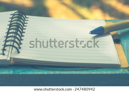 notebook and pen on wooden table in garden,vintage color tone. - stock photo