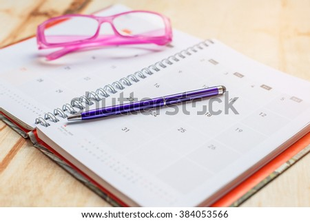 Notebook and pen with glasses on calendar format