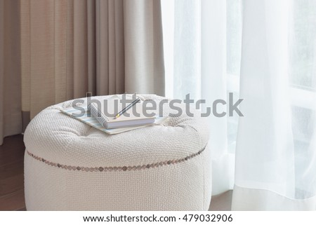 Notebook and pencil on beige color stool in the corner of living room - Upholstered Chair Stock Images, Royalty-Free Images & Vectors