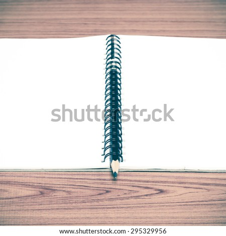notebook and pencil on wood background vintage style - stock photo