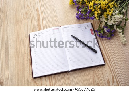Notebook and pencil on wooden table