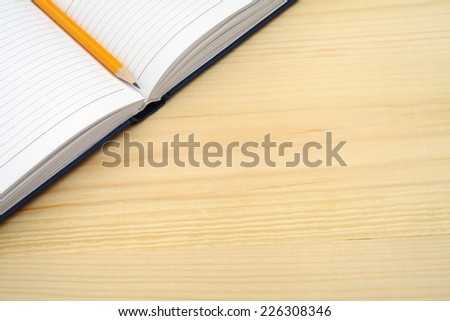 Notebook and pencil on wooden table with free text space. - stock photo