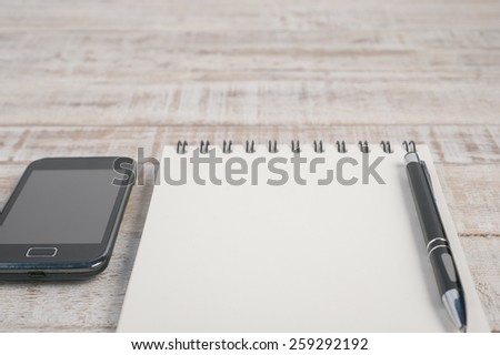 Notebook and phone on wood table for background - stock photo