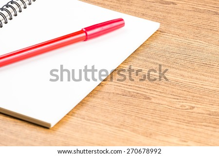 notebook and red pen on wooden table.education - stock photo