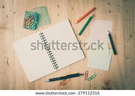 Notebook and sticky paper, paper clip, color pencil, and pen on wood table with film filter effect - stock photo