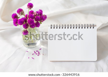 notebook and violet flower on table - stock photo