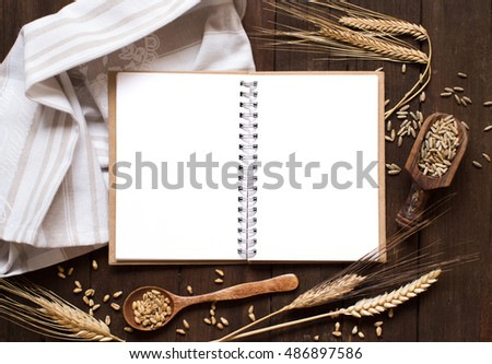 Notebook and wheat on a napkin with old wood background