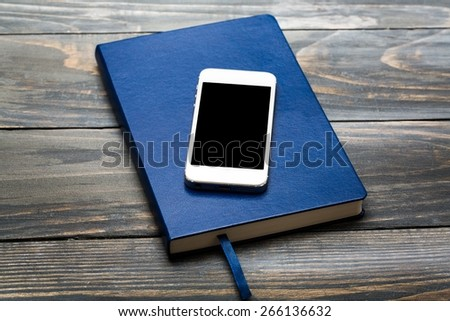 Notebook. Blank screen Smartphone on Brown Hard cover notebook with elastic strap on wooden table in perspective view,Template for adding your content - stock photo