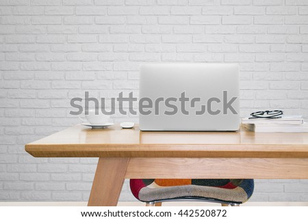notebook computer and a cup of coffee on working table, notebook computer, mouse, coffee, books, glasses, modern chair, white brick background - stock photo