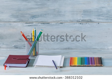 Notebook diary bright color pencils stationery on old wooden table vintage background - stock photo
