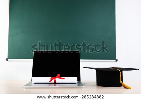 Notebook, diploma and master hat on desk in class on blackboard background - stock photo