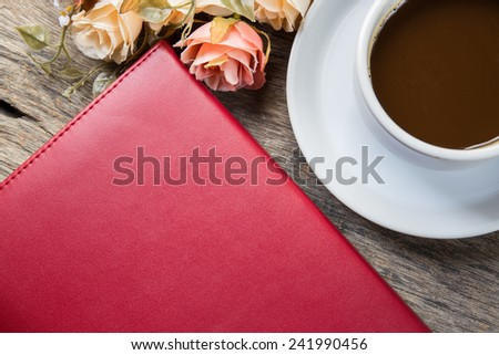 notebook, flower and cup of coffee on the desk - stock photo