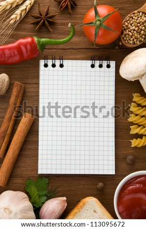 notebook for cooking recipes and spices on wooden table - stock photo