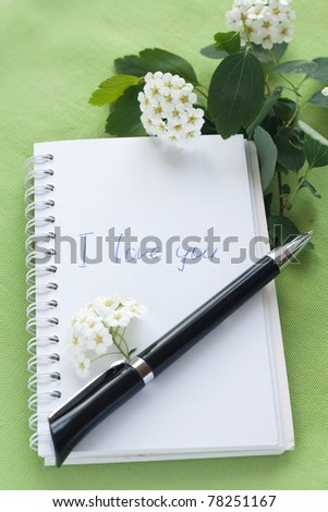 Notebook for notes, a pen and a branch with white flowers