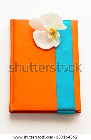 notebook in a red leather cover tied with a blue ribbon with an orchid as a gift - stock photo