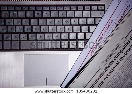 Notebook keyboard with a newspaper on it - stock photo