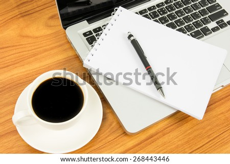 Notebook laptop and coffee cup on wood table