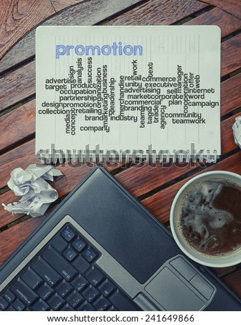 notebook lying on the table with the written words associated with the promotion , on the table are also laptop and cup of coffee, notes made in the form of the cloud of words