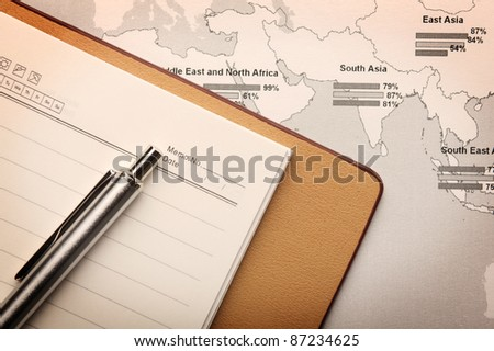 notebook on a map - stock photo