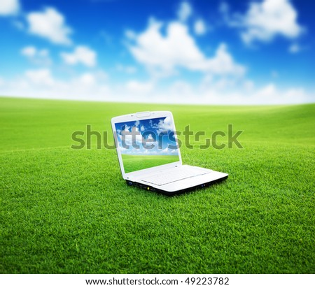 notebook on the green field of spring grass - stock photo