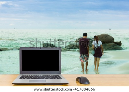Notebook on the table, blur image of the beach at Hua Hin,Thailand as background.